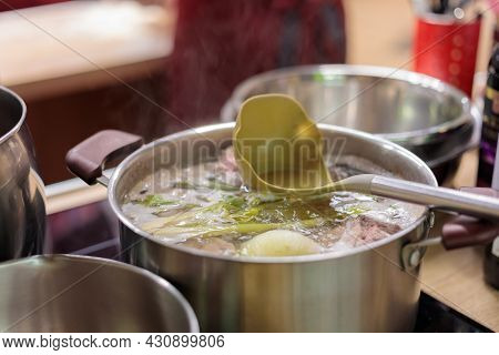 A Metal Saucepan Filled With Boiling Vegetable And Meat Broth. There Is A Scoop In The Broth. Close-