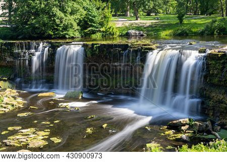 An Idyllic River Landscape In The Forest With A Waterfall
