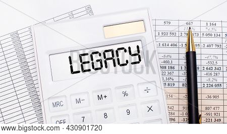 On The Desktop There Are Reports, A White Calculator With The Text Legacy On The Scoreboard And A Pe
