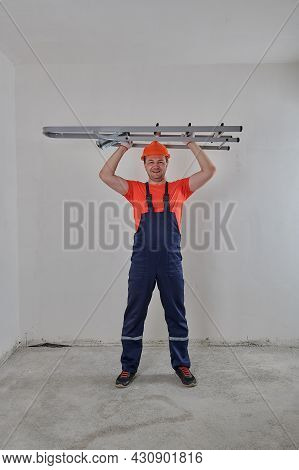 A Construction Worker In A Helmet Holds A Stepladder