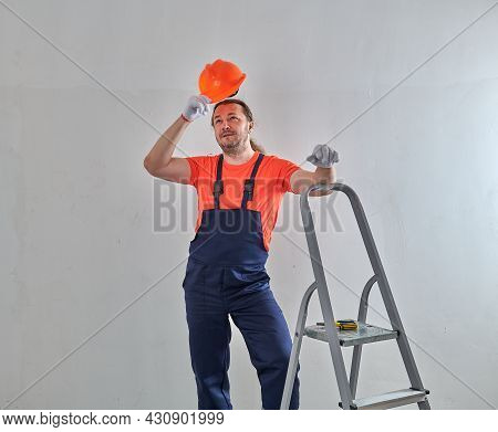 In A Helmet, The Foreman Leaned On A Metal Step-ladder