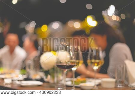 Glasses For Wine And People At Dinner Table With Blurred Background And Warm Lights. Elebrating Even