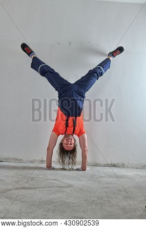 The Original Foreman In An Orange T-shirt Stands Upside Down