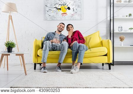 Cheerful Multiethnic Couple With Remote Controller Watching Movie At Home