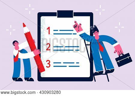 Time Management And List Of Tasks Concept. Two Business People Standing Around Huge List Of Work Dut
