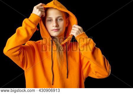 Shot Of Pretty Teenage Girl Putting The Hood On. Portrait Of Attractive Teenager Wearing Warm Orange
