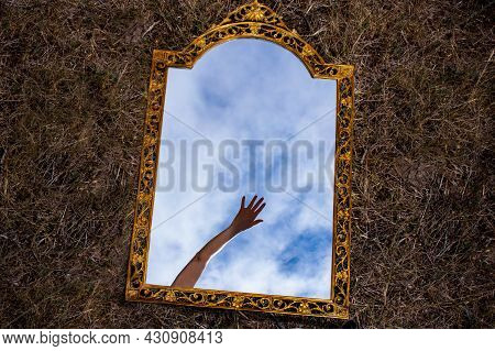 Vintage Gilded Mirror Lying On Dark Background Reflecting Mysterious Hand Reaching Out Over The Blue