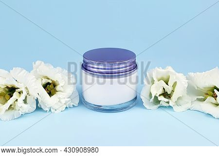 Glass Cosmetic Jar With White Cream, Blue Metal Screw Cap And White Lisianthus Flowers On Blue Backg