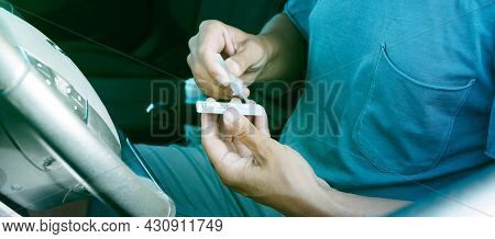 a young man places his own sample into the covid-19 antigen diagnostic test device while is sitting in the driver seat of his car, in a panoramic format to use as web banner or header