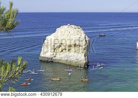 Rock Formations And People Doing Kayaks In The Atlantic Ocean To Visit The Benagil Caves, Algarve, P