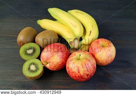 Assorted Fresh Ripe Fruits On Black Wooden Background With Cut Kiwifruit For The Concept Of Eating W