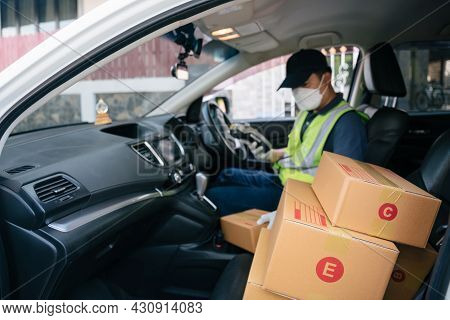 Select Focus A Box, A Delivery Man Using A Credit Card Reader. In The Van With Parcels On The Outsid