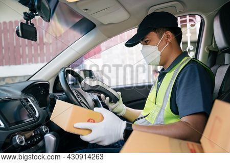 Asian Delivery Man Using A Credit Card Reader. In The Car With Parcels On The Outside Of The Warehou