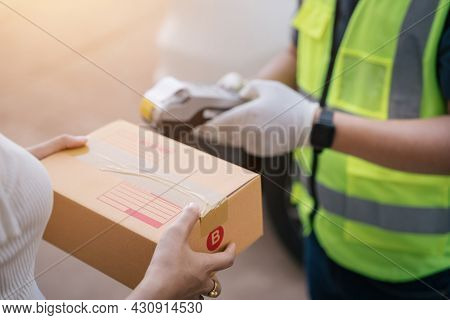 A Delivery Man Using A Credit Card Reader While Delivering Products To Customers At Home, Cash On De
