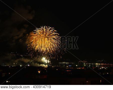 Bright Yellow Fireworks Flash With Sparkles In The Dark Night Sky Over A Seaside City. Selebrating V