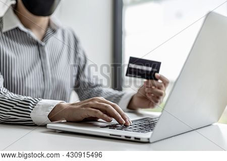 Woman Holding Credit Card And Typing On A Laptop Keyboard, She Is Filling Out Credit Card Informatio
