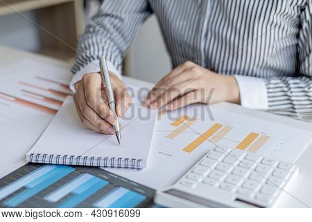 A Businesswoman Is Taking Notes In A Notebook, She Checks Company Financial Documents And She Takes