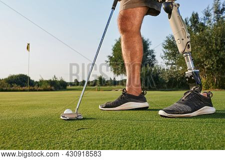 Professional Golfer With Prosthetic Leg Hitting With Putter On Golf Ball During Golfing. Concept Of
