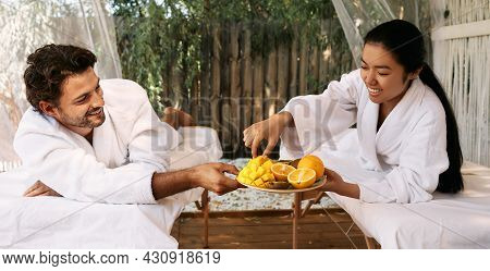 Asian Woman With Her Handsome Boyfriend Eating Exotic Fruits At Spa Resort. Couple While Romantic We