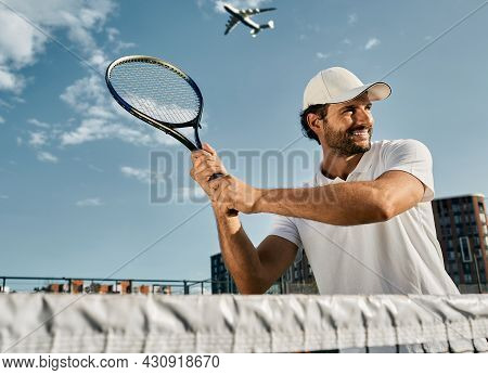 Handsome Tennis Player While Match Game With Tennis Racket In Hands Before Shot Over Background Of B