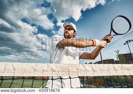 Tennis Player. Handsome Man Wearing White Tennis Uniform Plays Tennis Standing Near Tennis Net Over