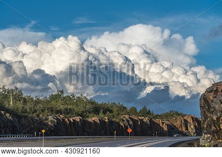 Sunlit White And Gray Clouds On Blue Sky Over Trans Canada Highway.
