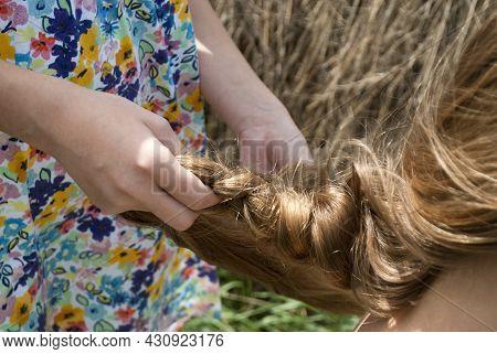 The Girl Weaves A Braid For Her Mother, Sister. Children's Hands Braiding Long Hair
