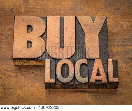 buy local - word abstract in vintage letterpress printing blocks against rustic wood, business and shopping concept