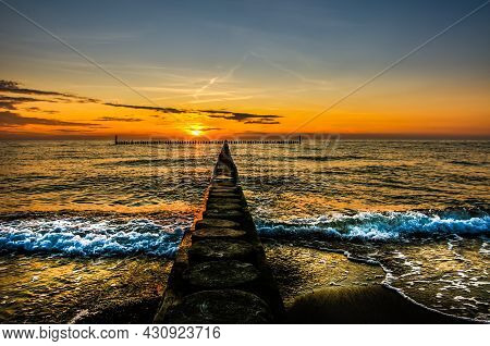 Beach By The Sea, Sunset Over A Wooden Breakwater, Baltic Sea