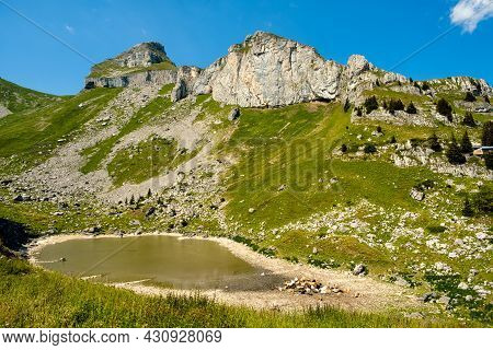 Beautiful View On The Mountain Lake Lac De Mayen Surrounded By Green Alpine Pastures And Steep Rocky