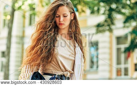 Portrait Of A Beautiful Young Woman In A Casual Outfit  Posing On The Street On A Sunny Day. Pretty