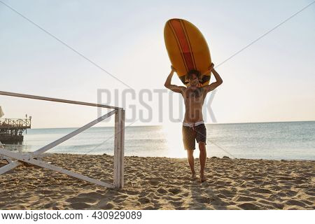 Young european surfer carrying surfboard on head on sandy beach coast. Curly man with tattoo wear swimming trunks. Concept of extreme water sport. Idea of summer vacation. Sunny day