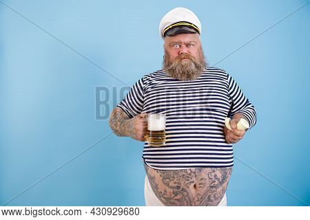 Funny Obese Sailor Holds Smoking Pipe And Beer Grimacing On Light Blue Background