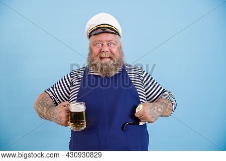 Funny Plump Person In Sailor Costume Holds Smoking Pipe And Beer On Light Blue Background