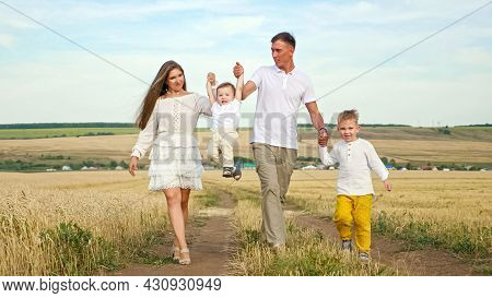 Family Couple In White Clothes Walks Joining Hands With Children And Lifts Toddler Son In Yellow Whe