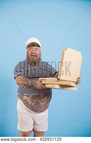 Happy Surprised Plump Man Sailor Holds Open Box Of Pizza On Light Blue Background