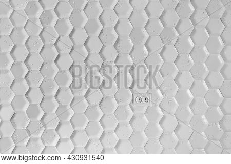 Electrical Outlet On The Wall Of White Tiles In The Form Of A Honeycomb. Gray Hexagon Background Wal