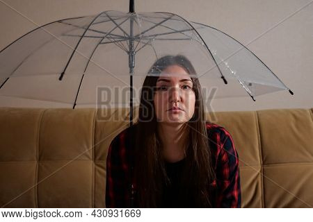 Pensive Brunette Woman In Checkered Shirt Hides From Water Flowing From Upstairs Neighbors Under Tra
