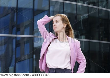 Young Beautiful Blonde Woman With Long Hair In Pink Elegant Clothes Stands Near A Modern Building Ma