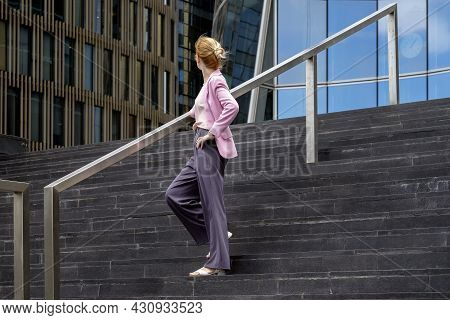 Young Blonde Of Millennium With Strict Hairstyle In Pink Elegant Clothes Stands On Steps Near Modern