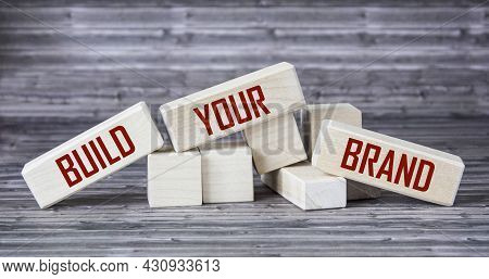Conceptual Image, Word Build Your Brand On Wooden Blocks And Wooden Table.