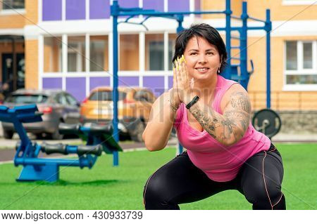 Strong Plump Woman Doing Squats On A Sports Ground In The Courtyard Of A City House Against The Back