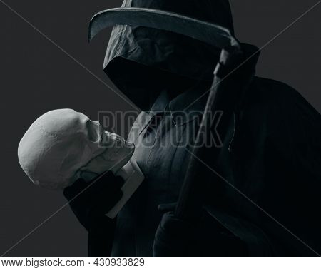 Grim Reaper With A Scythe Looking At Skull.