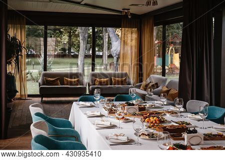 Long Table Before Celebration In Restaurant, Empty Glasses And Appetizers, Beg Terrace Windows. Cozy