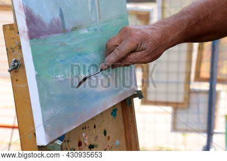Close Up Of A Male Person Hand Painting On Canvas