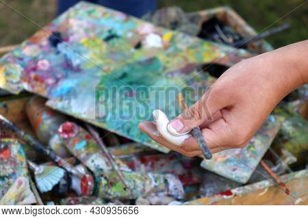 Female Artist With Palette And Brushes In Hand. Close-up
