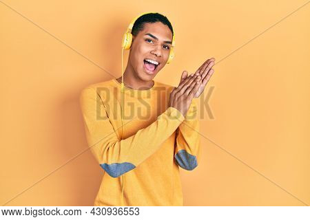 Young african american guy listening to music using headphones clapping and applauding happy and joyful, smiling proud hands together