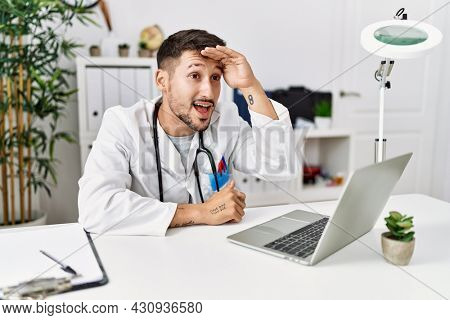 Young doctor working at the clinic using computer laptop very happy and smiling looking far away with hand over head. searching concept.