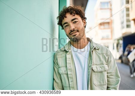Handsome hispanic man with beard smiling happy outdoors on a sunny day leaning on a wall