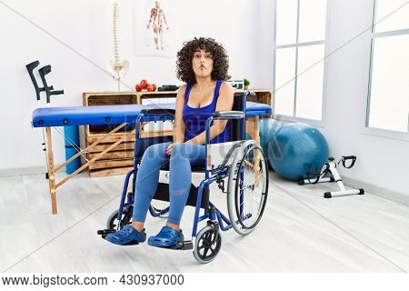 Young middle eastern woman sitting on wheelchair at physiotherapy clinic making fish face with lips, crazy and comical gesture. funny expression.